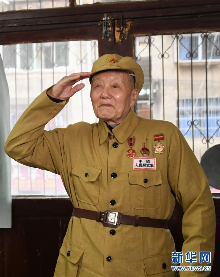 张富清穿上老式军装敬军礼(3月31日摄)。新华社记者 程敏 摄